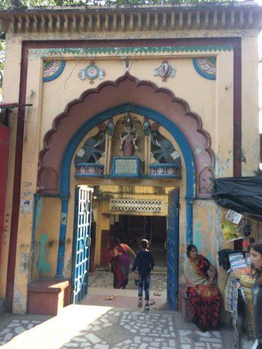 An Indian woman and child enter an ashram
