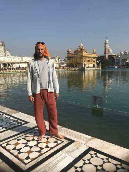 A traveller poses for a photograph at the Golden Temple in Amritsar